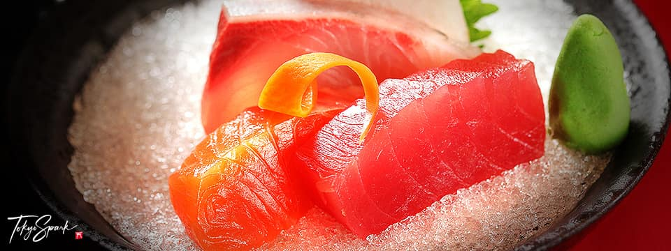 Sashimi on ice in a dark bowl